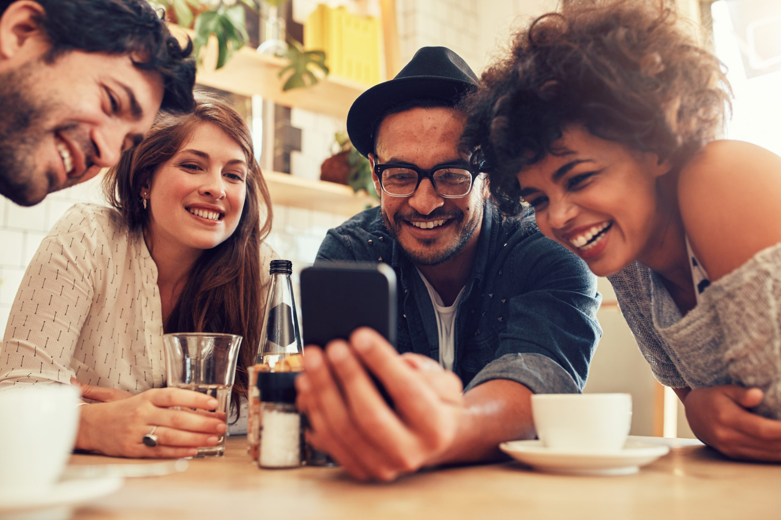 Group of friends sitting together in a cafe looking at mobile phone